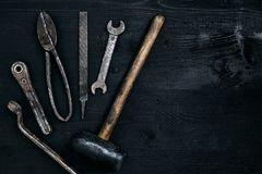 Old, rusty tools lying on a black wooden table. Hammer, chisel, metal scissors, wrench. Top view. Copy space. Still life. Flat lay royalty free stock image