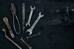 Old, rusty tools lying on a black wooden table. Hammer, chisel, metal scissors, wrench. Top view. Copy space. Still life. Flat lay stock photography