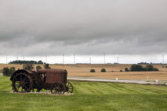 Old rusty tractor. With wind turbines in the background Stock Photos