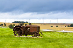 Old rusty tractor. With wind turbines in the background Royalty Free Stock Photography