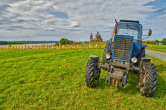 Old rusty tractor on a field with monastery in background Royalty Free Stock Images