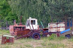 Old rusty tractor with a trailer and scrap metal in a field near trees. Broken retro technique at the scrap heap Royalty Free Stock Images