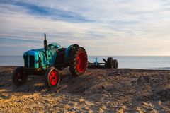 Old rusty tractor on the empty Cromer beach, Great Britain stock images