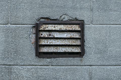 Old rusty ventilation grille on plastered wall Stock Image