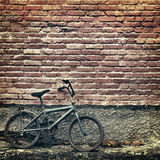 Old rusty vintage bicycle leaning against a brick wall Royalty Free Stock Photo