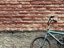 Old rusty vintage bicycle leaning against a brick wall Stock Photo