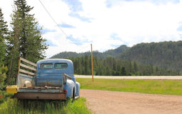 Old rusty vintage pickup by the road. Old blue rusty vintage pickup car in the countryside Royalty Free Stock Photography