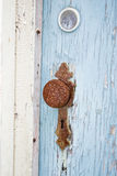 Old Rusty Vintage Round Door Knob. Vintage rusty door knob handle on old blue wooden door of old abandoned house. Weathered door handle with rusty keyhole Royalty Free Stock Photography