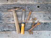 Old rusty vintage tools on weathered grey wood background Royalty Free Stock Photos