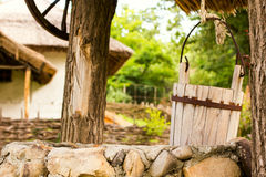 Old rusty vintage water well  with rural background.Focus on wooden bucket Stock Photos