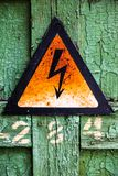 Old rusty warning high voltage sign on cracked wooden surface Stock Photo