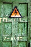 Old rusty warning high voltage sign on cracked wooden surface. Old rusty warning high voltage sign on cracked green wooden surface Royalty Free Stock Photo