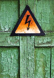 Old rusty warning high voltage sign on cracked wooden surface. Old rusty warning high voltage sign on cracked green wooden surface Royalty Free Stock Image