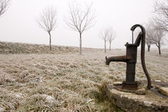 Old rusty water pump on the countryside in winter Royalty Free Stock Photos