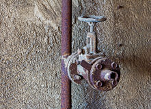 Old rusty water tap in concrete wall Stock Images