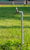 Old rusty water taps in Blurred Background. Old rusty water taps in Blurred Green Lawn Background Stock Images
