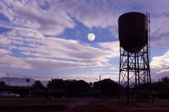 Old and rusty water tower on a blue sky and moon Stock Images