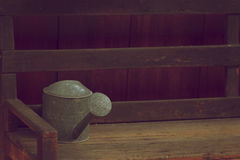 Old and rusty watering can place on wooden chair Stock Photos