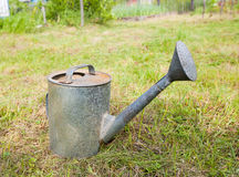 Old, rusty watering can standing on grass Royalty Free Stock Images