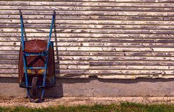 Old rusty wheelbarrow. Besides wooden wall Royalty Free Stock Image