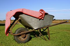 Old rusty wheelbarrow covered by gingham Royalty Free Stock Images