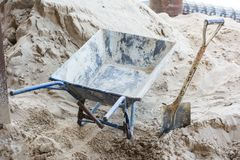 Old rusty wheelbarrow, Iron cart with shovel on sand. Stock Photography