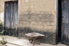 Old wheelbarrow leaning against apparent plaster wall Royalty Free Stock Photo