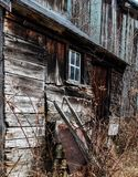 Old rusty Wheelbarrow leans against decrepit barn. Overgrown Wooden barn, dilapidated, window,  right winter Stock Photos