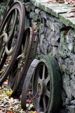 Old rusty wheels set against stone wall Royalty Free Stock Photo