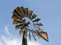 Old Rusty Windmill. An old metal windmill against a blue sky with wispy clouds Stock Image