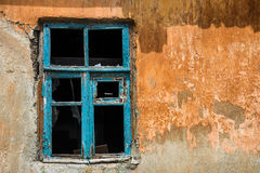 Old rusty window in devastated house. Window in devastated house with yellow wall royalty free stock photos