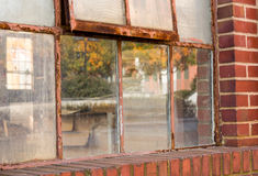 Old rusty window in warehouse reflecting fall Stock Photo