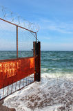 Old rusty wire fence on a seashore. Restricted area on a beach Royalty Free Stock Images