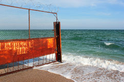 Old rusty wire fence on a seashore. Restricted area on a beach Royalty Free Stock Photos