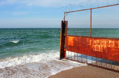 Old rusty wire fence on a seashore. Restricted area on a beach Stock Photos