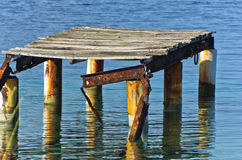 Old rusty wooden dock at sunny morning near the entrance to Porto Koufo harbor Royalty Free Stock Photos