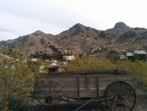 Old, rusty wooden wagon in a desert landscape. With mountains and structures in the background stock images