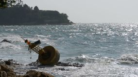 Old Rusty Yellow Buoy Lies on the Shore of a Rocky Beach. Thailand. Pattaya. Asia. Old Rusty Yellow Buoy Lies on the Shore of a Rocky Beach against the stock video