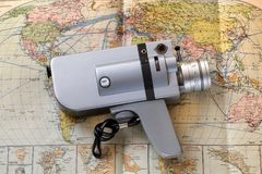 Travel,holiday with camera movie vintage on a retro and vintage world map. An old 50`s camcorder mixes the colors of the past with the memories of entire Stock Image
