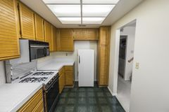Old 1980s Condo Kitchen. With oak cabinets, tile countertops, gas stove and green flooring stock image