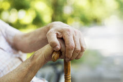 An old's man hands holding cane. Close up concept. Stock Image