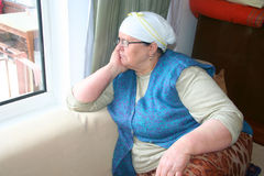 Old sad lady. Waiting her memories near window Royalty Free Stock Photography