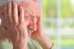 Old sad man on the window background Royalty Free Stock Image