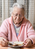 Old sad woman eating at home Royalty Free Stock Photography