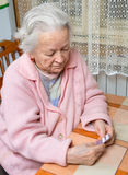 Old sad woman holding pills. In hands at home Stock Photos