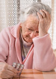 Old sad woman holding pills. At home Royalty Free Stock Image