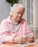 Old sad woman holding pills Royalty Free Stock Photography