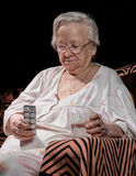 Old sad woman holding pills. Old sick woman with pills and glass of water at home Stock Images