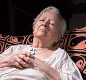 Old sad woman holding pills. Old sick woman with pills at home Royalty Free Stock Photography