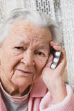 Old sad woman with pills at home. Worried about having to take too many pills Royalty Free Stock Images